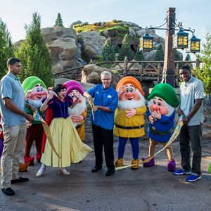 1 of 2: Fantasyland - Snow White and the Seven Dwarfs join Phil Holmes (center), vice president of Magic Kingdom Park, and Orlando Magic players Tobias Harris (left) and Victor Oladipo (right)