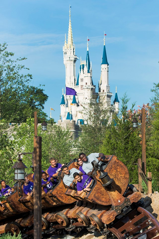 Adults and kids from Big Brothers Big Sisters of Central Florida and Orlando Magic players Tobias Harris (left) and Victor Oladipo (right) aboard Seven Dwarfs Mine Train