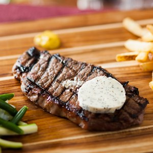 5 of 10: Be Our Guest Restaurant - Be Our Guest Restaurant menu item - Grilled Strip Steak with garlic-herb butter and pommes frites
