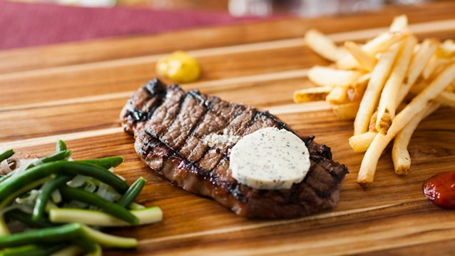 Be Our Guest Restaurant - Be Our Guest Restaurant menu item - Grilled Strip Steak with garlic-herb butter and pommes frites