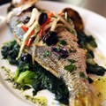 Kouzzina by Cat Cora - TRADITIONAL WHOLE FISH: At Kouzzina by Cat Cora at Disney's BoardWalk Resort, whole fish is pan roasted and served with braised greens, Greek olives, fennel and smoked chili. Copyright 2009 The Walt Disney Co.
