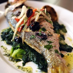 2 of 10: Kouzzina by Cat Cora - TRADITIONAL WHOLE FISH: At Kouzzina by Cat Cora at Disney's BoardWalk Resort, whole fish is pan roasted and served with braised greens, Greek olives, fennel and smoked chili. Copyright 2009 The Walt Disney Co.