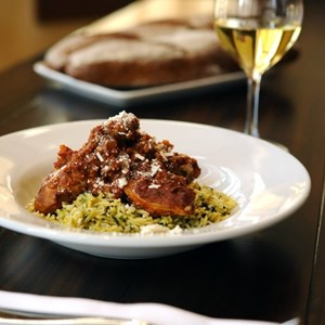 6 of 10: Kouzzina by Cat Cora - CINNAMON-STEWED CHICKEN: A signature dish at Kouzzina by Cat Cora at Disney's BoardWalk Resort with tomatoes, herbed orzo and Mizithra cheese. Copyright 2009 The Walt Disney Co.