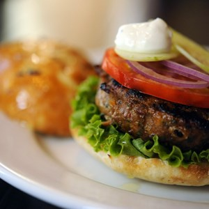 7 of 10: Kouzzina by Cat Cora - CHAR-GRILLED LAMB BURGER: The burger at Kouzzina by Cat Cora at Disney's BoardWalk is made with lamb and dressed with olives and feta, with a side of crisp sweet potato fries. Copyright 2009 The Walt Disney Co.