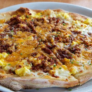 1 of 5: Wolfgang Puck Express - Marketplace - Wolfgang Puck Express Marketplace breakfast - Breakfast Pizza, scrambled eggs, bacon, tomatoes, mozzarella, cheddar, caramelized onions $11