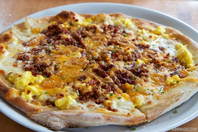 Wolfgang Puck Express - Marketplace - Wolfgang Puck Express Marketplace breakfast - Breakfast Pizza, scrambled eggs, bacon, tomatoes, mozzarella, cheddar, caramelized onions $11