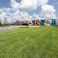 Disney's Art of Animation Resort - Main entrance area, bus stops to the left, arriving guests drop-off to the right