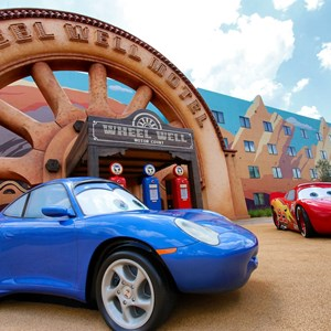 29 of 33: Disney's Art of Animation Resort - Lightning McQueen and Sally Carrera in front of the Wheel Well Motel building in Cars section at Disney's Art of Animation Resort